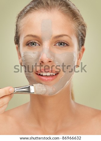 closeup beauty portrait of beautiful blonde woman applying a facial mud mask on her skin with a brush, smiling - stock photo