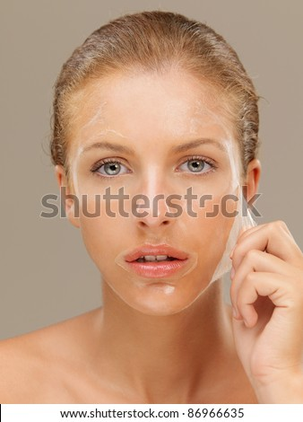 closeup beauty portrait of beautiful blonde woman peeling off a facial mask - stock photo