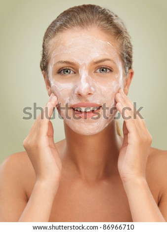 closeup beauty portrait of beautiful blonde woman with a facial moisturizer mask on her skin, touching her face smiling - stock photo