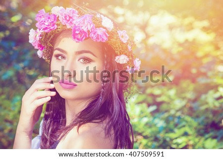 Closeup beauty portrait of young brunette woman wearing makeup and pink roses wreath on her head. Soft hues, retouched, natural light. - stock photo
