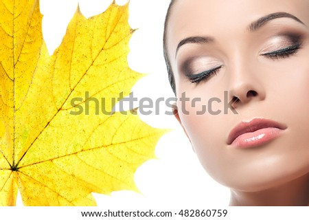 closeup beauty portrait of young caucasian woman face skin makeup eyes closed lips brunette isolated on white studio shot autumn leave yellow