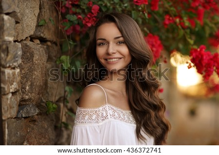 Closeup beauty portrait of young pretty happy smiling girl with dark curly hair looking at you. Soft sunset backligth - stock photo