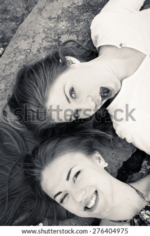 Closeup black and white picture of pretty girl friends relaxing head to head happy smiling - stock photo