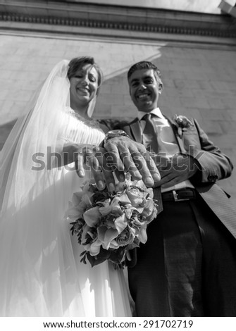 Closeup black and white portrait of newly married couple showing golden rings