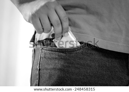 Closeup black and white shot of man putting condom in jeans pocket - stock photo