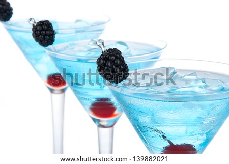 Closeup blue martini cocktails row composition with alcohol, maraschino cherry, blackberry, vodka, curacao and crushed ice on a white background - stock photo