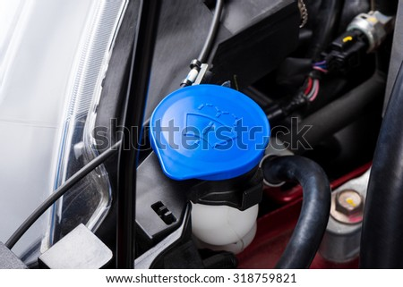 closeup blue windshield washer fluid reservoir cap in engine room - stock photo