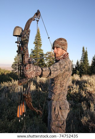 closeup bow hunter dressed in camouflage pulling bow back in woods - stock photo