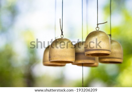 Closeup brass wind chimes in the garden - stock photo