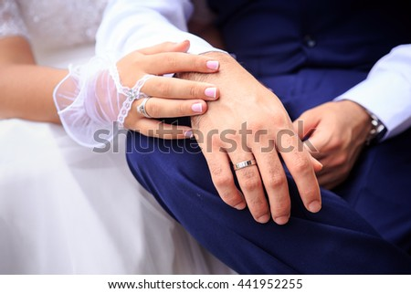 closeup bride in white dress and groom in dark blue suit sit hands lie on his knee  - stock photo