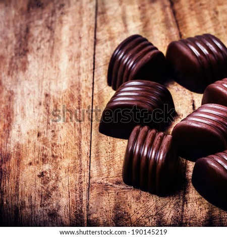 Closeup brown chocolate candy background. Chocolate truffles on wooden table with copyspace.  - stock photo