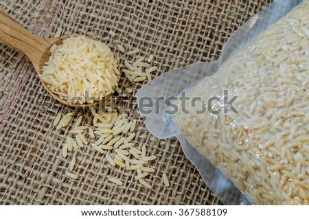 Closeup brown rice in vacuum packaging and  brown rice in a wooden spoon on burlap background. - stock photo