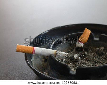 Closeup burning cigarette in ashtray and smoke on the table - stock photo