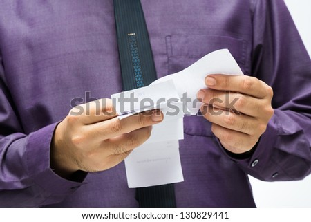 Closeup businessman hand checking receipts in hand - stock photo