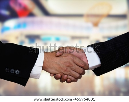 closeup businessman handshake with blurred superstore background, business collaboration concept - stock photo