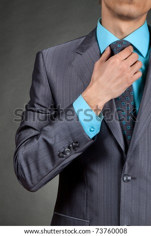 closeup businessman suit in a suit straightens his tie over gray background