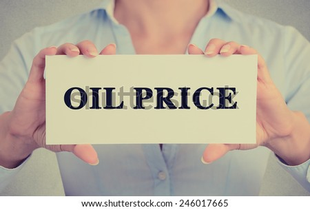 Closeup businesswoman hands holding white card sign with oil price text message isolated on grey wall office background. Retro instagram style image - stock photo