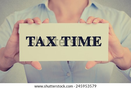 Closeup businesswoman hands holding white card sign with tax time text message isolated on grey wall office background. Retro instagram style image - stock photo