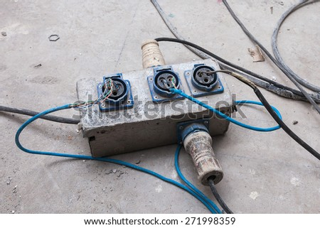 closeup cable electrical plug in the electric extension cord on floor workplace - stock photo