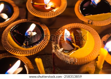 Closeup candles flame in clay pot for meditation at night. - stock photo