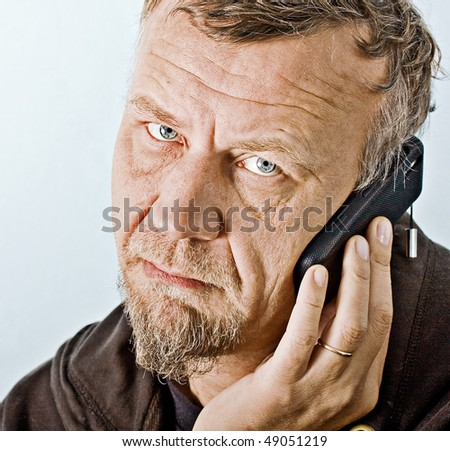 Closeup character portrait of a man with blue eyes, dressed in an old hooded jacket looking at the camera with questioning and suspicious facial expression while making a telephone call - stock photo