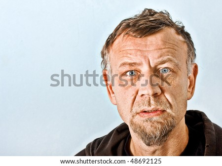 Closeup character portrait of a man with blue eyes looking at the camera with questioning and suspicious facial expression - stock photo