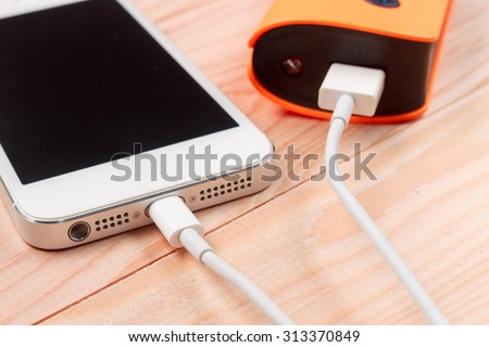 Closeup Charging Smartphone on wooden background - stock photo