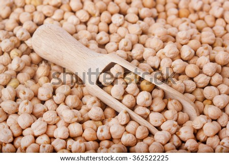 Closeup chickpea in wooden spoon and heap chickpea background - stock photo