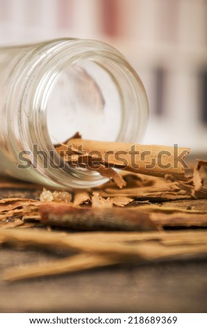 closeup cinnamon sticks in a jar on wooden table selective focus - stock photo