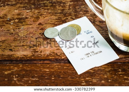 Closeup coffee receipt and coin tip on wood table - stock photo