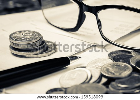 Closeup coins on receipts with pen and eyeglasses - stock photo