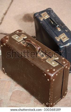 Closeup collection of two beautiful old fashioned vintage brown blue suitcases with handles metal buttonheads and keylocks made of leather standing over stone tile floor background, vertical picture