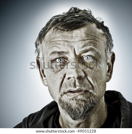 Closeup color processed character portrait of a man with blue eyes, dressed in an old hooded jacket looking at the camera with questioning and suspicious facial expression - stock photo