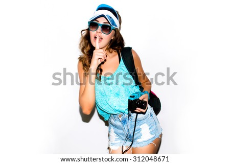 Closeup colored vintage portrait of sexy smiling photographer girl,holding and making picture on retro vintage camera,wearing swag colored cap,amazing woman posing on  white wall, joy and happiness - stock photo