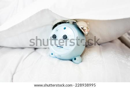Closeup conceptual photo of alarm clock under pillow on bed - stock photo