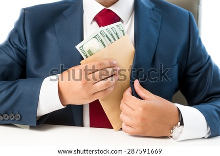 Closeup conceptual photo of bribed man putting money in the suit pocket - stock photo