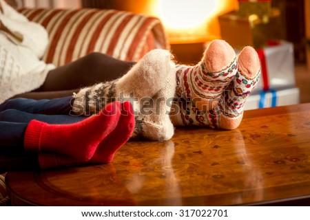Closeup conceptual photo of family warming feet at fireplace - stock photo