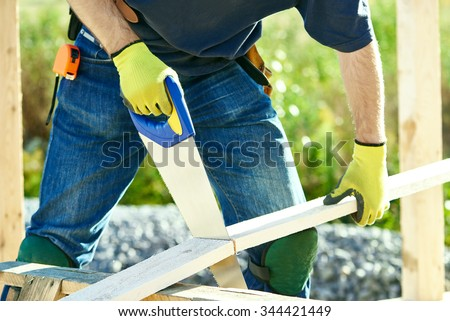 Closeup construction roofer carpenter worker sawing wood board with hand saw outdoors - stock photo