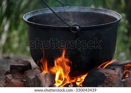 Closeup cooking in cauldron licked by flames on open fire fireplace made of bricks stones in field conditions over blurred nature background, horizontal picture - stock photo