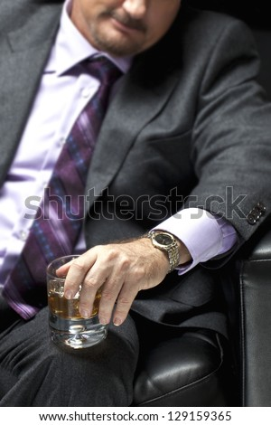 Closeup cropped shot of a gangster in full suit holding whiskey glass in hand