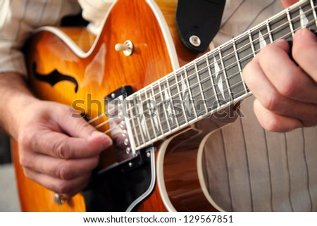 Closeup cropped view of the hands of a man playing a wooden guitar strumming a tune on the strings