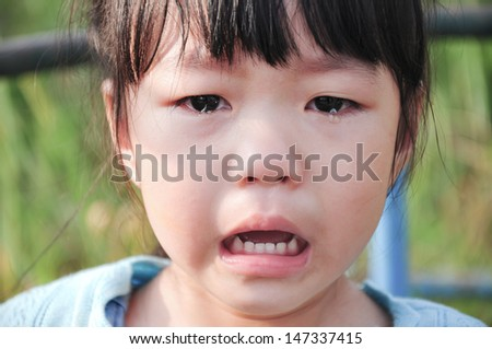 closeup crying kid with tears on her eyes. - stock photo