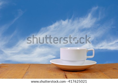 Closeup cup of coffee on balcony, nature blue sky background. - stock photo