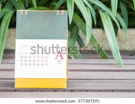 Closeup cute calendar in april on blurred garden view background - stock photo