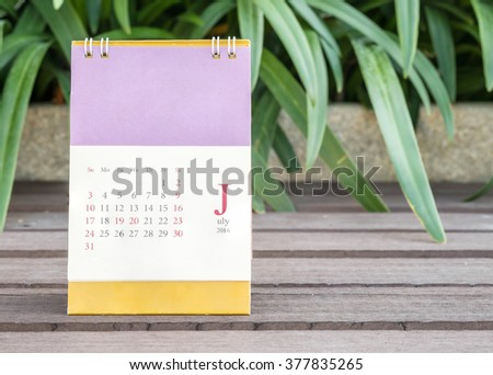 Closeup cute calendar in july on blurred garden view background - stock photo