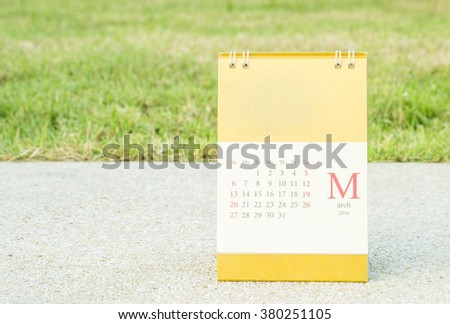 Closeup cute calendar in march on blurred stone floor and green grass in the garden view in the evening background - stock photo