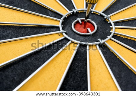 Closeup dart target with arrow on the center bullseye of dartboard, Goal target marketing success business investment financial strategy concept, abstract background - stock photo
