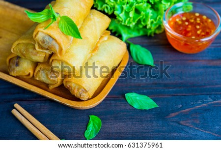 closeup deep fried spring rolls in wooden tray with sauce place on black table
