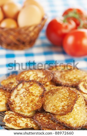 closeup delicious fried fritter, twig red tomatoes,wicker basket eggs background tablecloth blue cell - stock photo