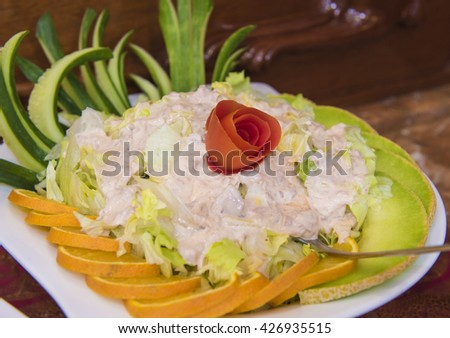 Closeup detail of a fresh salad dish with melon and orange on a white plate. - stock photo